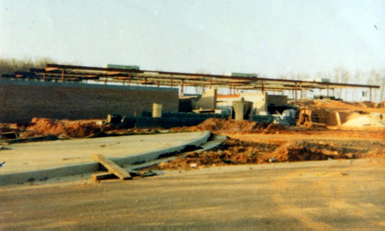 Color photograph of Laurel Ridge Elementary School during construction. Some cinderblock walls and steel framing are in place. Construction supplies and equipment are spread throughout the site.
